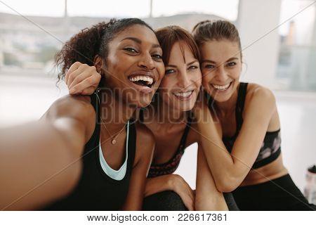 Smiling Women Friends Taking Selfie In Fitness Studio
