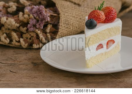 Strawberry Shortcake On White Plate Put On Wood Table With Copy Space. Delicious And Soft Vanilla Sp