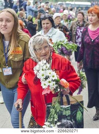Pyatigorsk, Russia - May 09, 2017: War Veteran Woman With Flowers On The Victory Day Celebration. Ru