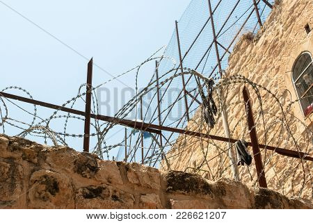 Horizontal Picture Of Brick Wall With Barbwire In Hebron, Located In West Bank, Israel.