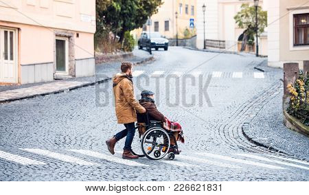 Father In Wheelchair And Young Son On A Walk, Crossing The Road. A Carer Assisting Disabled Senior M