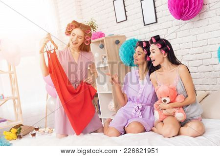 Three Girls With Curlers In Their Hair Looking At New Dress. They Are Celebrating Women's Day March