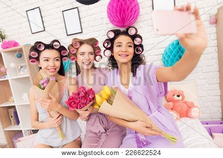 Three Girls With Curlers In Their Hair And Flowers In Hands Taking Selfie. They Are Celebrating Wome