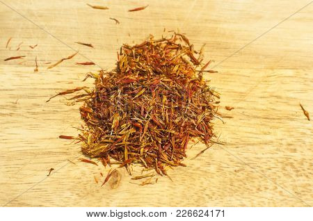 A Pile Of Dry Delicate Saffron Threads, Plucked From Crocus Flowers Closeup On Wooden Board Backgrou