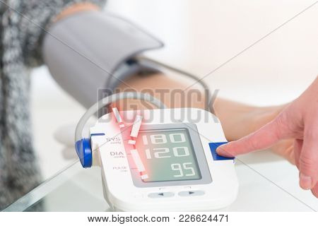 Doctor cardiologist measuring blood pressure of female patient in hospital office appointment, too high blood pressure is showing on the screen of the meter