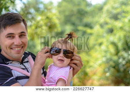 Little Wonder Girl In A Pink Dress And Sunglasses Is Playing With Her Young Father