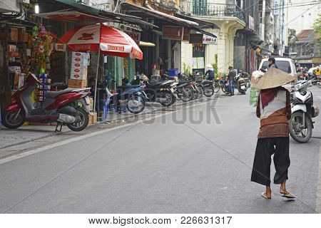 Hanoi, Vietnam - December 14th 2017. An Eldery Woman In Traditional Clothes And Hat Walks Down A Str
