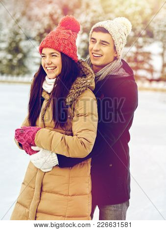 people, winter, love and leisure concept - happy couple hugging ice skating on rink outdoors