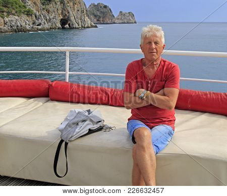 Russian Tourist Against The Background Of Sea And Rocks Nearby Alanya, Turkey