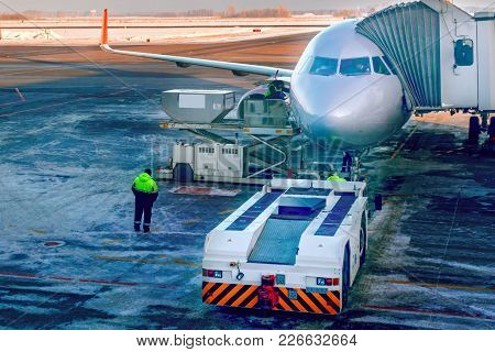 Aircraft Being Attached To Jetway Or Passenger Telescopic Gangway On Airport Apron. Prepares For Boa