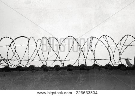 The Close-up Of A Barbed Wire Fence On The Top Of A Wall.