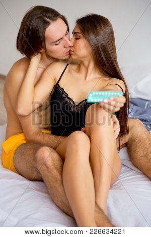 A Portrait Of A Girl Holding Contraceptive Pills In Bed