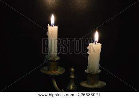 White Candles On A Black Table (on Fire)