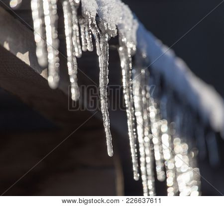 Long And Dangerous Icicles On A House Roof .