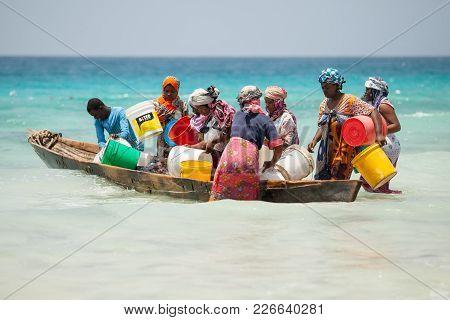 Stone Town, Zanzibar Island, Tanzania, 05/28/2015.  Women Gathering Small Fish In A Boat Of The Coas