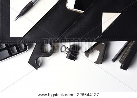 Office Supplies: Overhead shot of a white desk with open folio with various office tools, and calculator, cell phone, pen and blank cards. Horizontal with copy space.