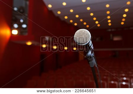 Microphone Close-up On The Background Of A Dark Auditorium. A Press Conference Or Concert