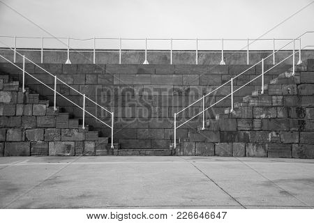 Photo In Black And White Of A Stone Wall With White Railing And Sunlight