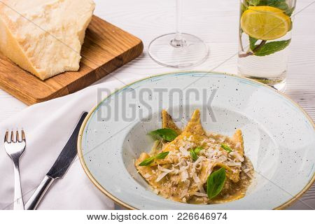 Ravioli Pasta With Basil And Parmesan Cheese On Plate. Parmesan With A Grater On A Cutting Board. Wh