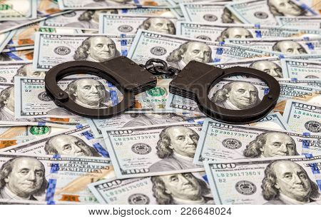 Steel Black Handcuffs Lying On The Background Of American Dollars