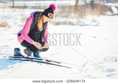 Woman cross country skier putting on ski on the slope