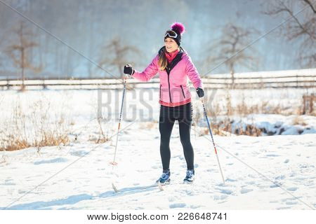 Woman doing cross country skiing as winter sport in snow landscape