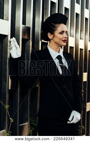 Attractive Young Woman Stewardess In Uniform Waiting For Her Flight