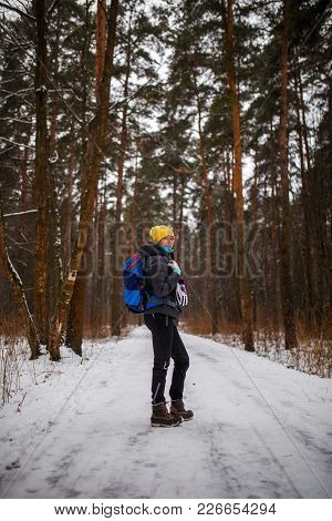 Side View Of Woman With Backpack Over Winter Forest In Afternoon
