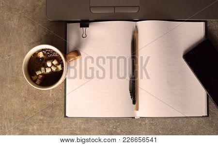 Grey Brown Grunge Table With Laptop, Coffee Cup, Clips, Notebook, Pen, Penclil. Top View With Copy S