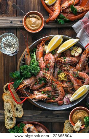 Paella Pan With Roasted Tiger Shrimps And Many Dishes, Bread And Wine.