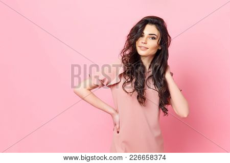 Beautiful Fashionable Girl With Long Curly Hair In A Pink Dress In The Studio On A Pink Background.