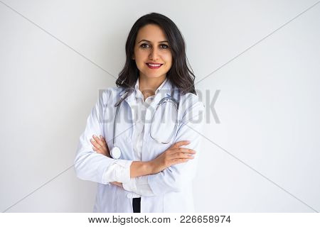 Closeup Portrait Of Smiling Beautiful Dark-haired Female Doctor Looking At Camera And Standing With