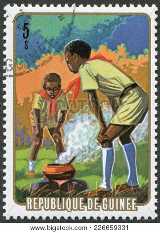 Guinea - Circa 1974: Postage Stamps Printed In The Republic Of Guinea, Shows The Boy Scouts For Cook