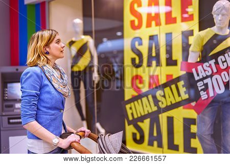 Young Beautiful Woman With Stroller Looking At Showcase With Discounts In Shopping Center