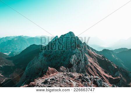 Jagged rocky ridge and high mountain peak summit in a misty atmospheric alpine landscape