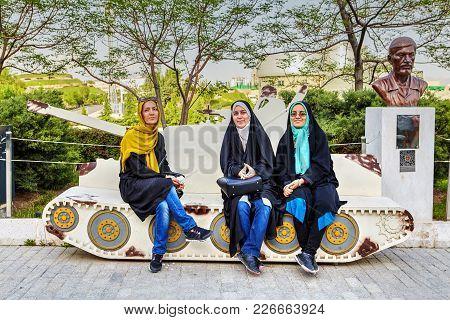 Tehran, Iran - April 28, 2017: Three Young Iranian Girls In Hijabs Are Sitting On The Breadboard Mod
