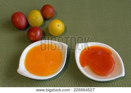Two Egg Yolks - Orange And Red, Of Hen Fed With Red Peppers. And Cherry Tomatoes To Compare Colors.