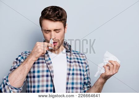 Portrait Of Attractive Guy With A Nasal Spray And Tissue In Hands, Using Nose Drops Over Grey Backgr