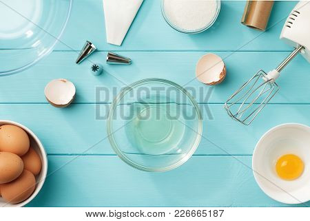 Culinary Background With Separated Egg Whites And Yolks In The Bowls On Blue Wooden Table. Step By S