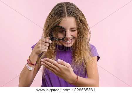 Cheerful Teen Girl With Long Blond Curly Hair Looking Through A Magnifying Glass