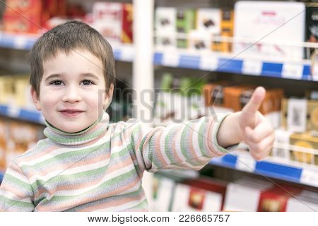 Happy Boy 4 Years In A Supermarket On The Background Of Shelves With Chocolate.