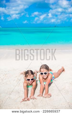 Adorable Little Sisters At Beach During Summer Vacation