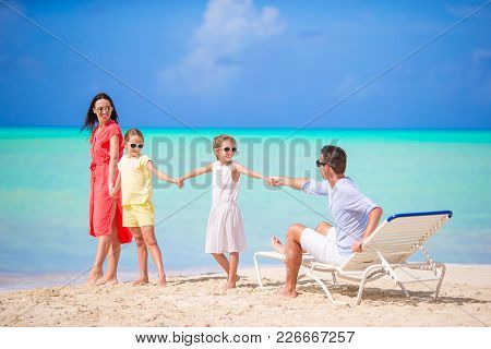 Happy Beautiful Family Of Four On White Beach