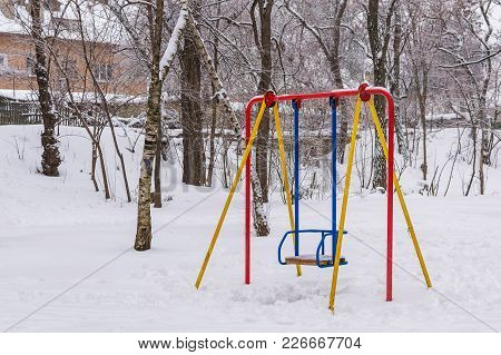 Children Swing In Park Under The Snow After The Strongest Snowfall