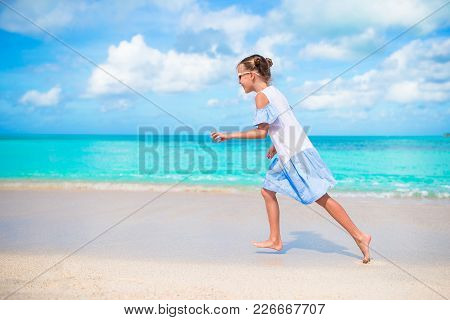 Happy Little Girl Running And Splashing At Shallow Water At Beach Having A Lot Of Fun