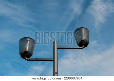 Street Lamp Post Againt The Blue Sky With Clouds. Cracked Lamp. Compact Fluorescent Lighting Bulb