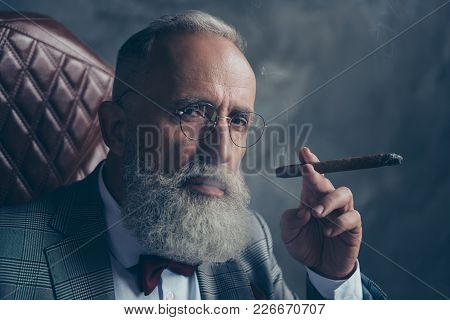 Close Up Portrait Of Harsh, Brutal, Old Shareholder In Glasses, Holding Cigar, Looking At Camera Wit