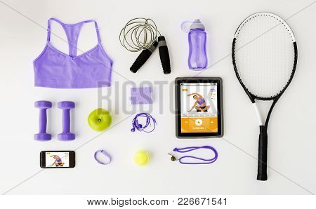 fitness, healthy lifestyle, technology and objects concept - tablet pc computer with smartphone and sports stuff in trendy ultra violet color on white background