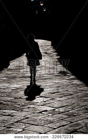 Silhouette Of Woman Walking Through The Ancient Streets Of Florence In Italy