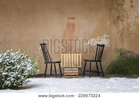 Table Made Of Two Boxes And Two Chairs Near The Grunge Dirty Wall